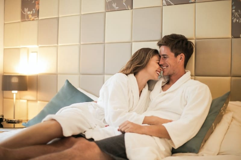 man and woman cuddling while lying on bed
