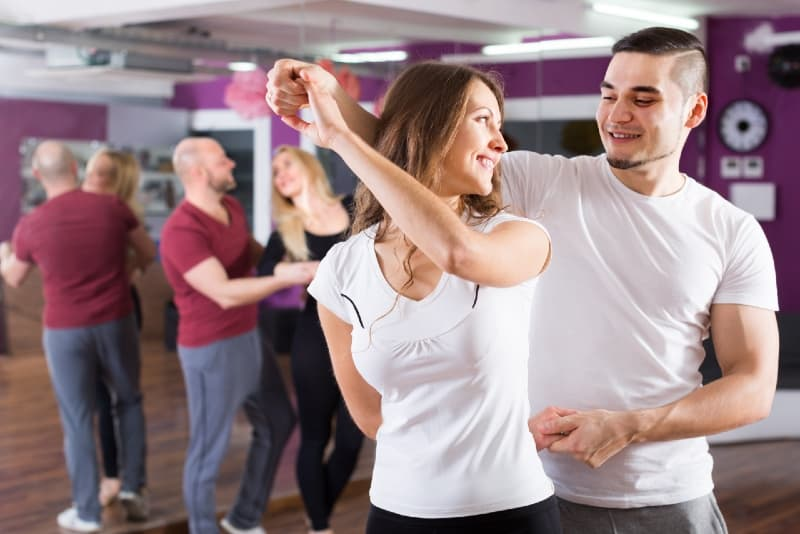 man and woman in white t-shirts dancing indoor