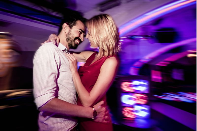 couple dancing in a pub with focus on the couple and a blurred background