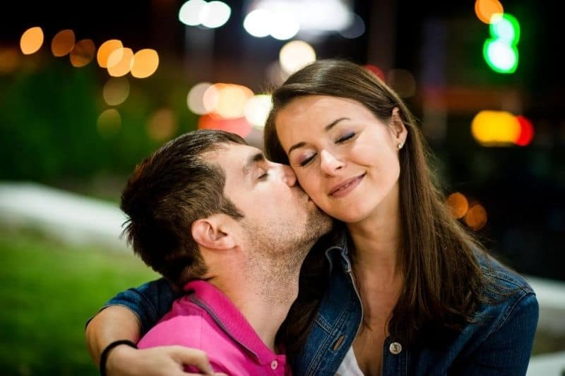 couple dating at night outdoors man kissing the woman's cheek