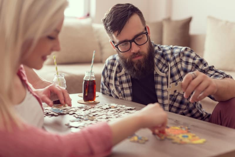 man and woman doing puzzle while sitting on floor