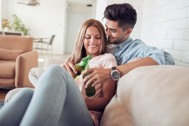 man and woman drinking beer while sitting on sofa