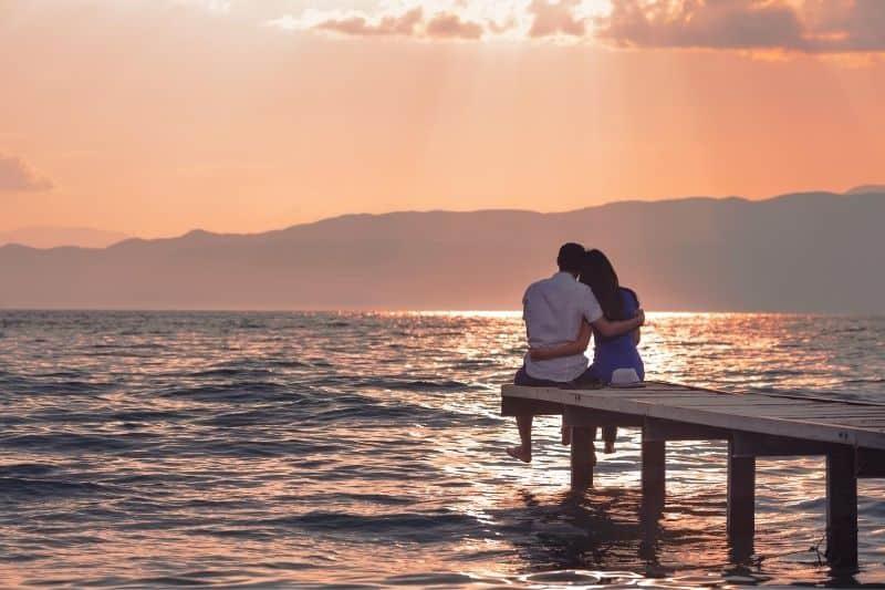 couple enjoying sunset sitting on the wooden platform on the sea
