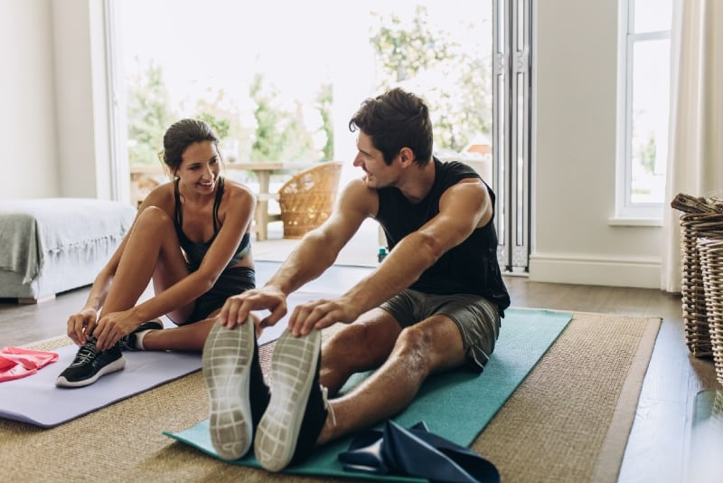 man and woman in sports wear exercising at home