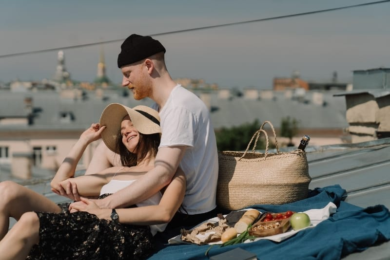 man in white t-shirt and woman having picnic on rooftop
