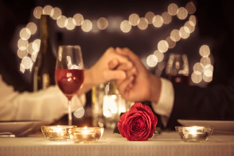 man and woman holding hands near red rose