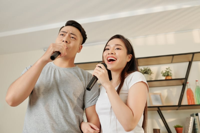 man and woman holding microphones and singing indoor