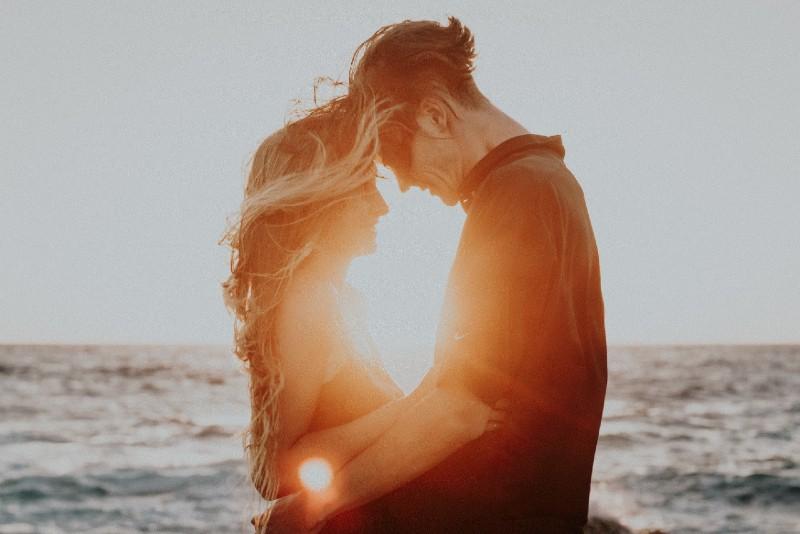 man and woman hugging near sea