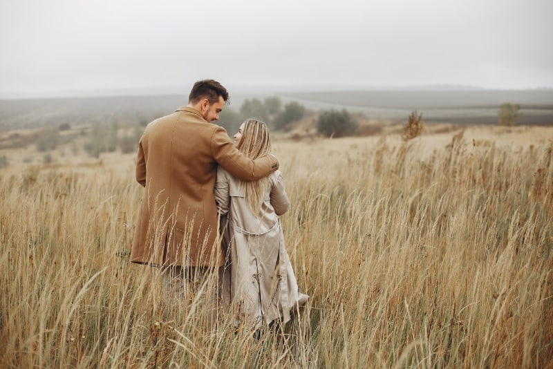 man and woman hugging in dry field