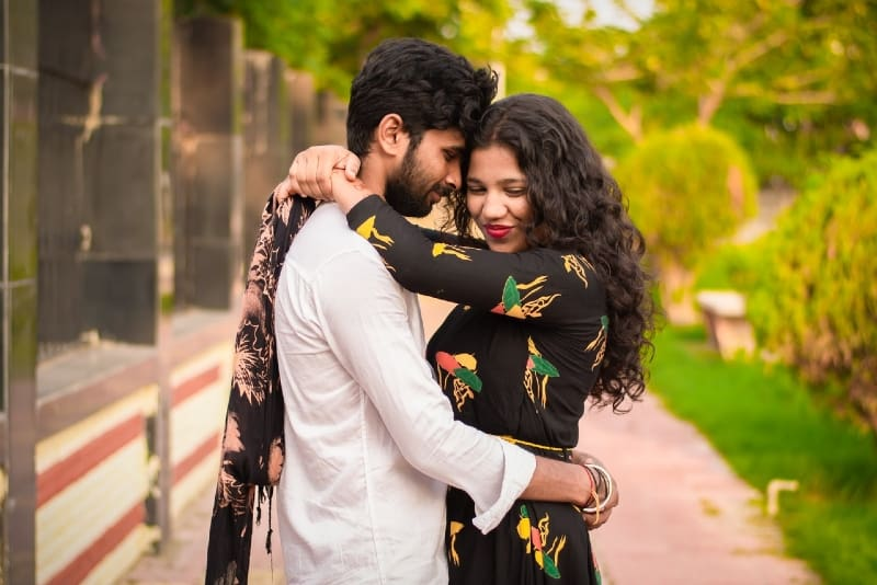woman in black printed dress and man hugging outdoor
