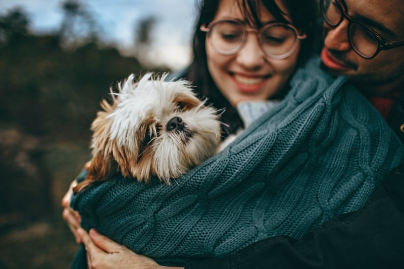 man and woman with eyeglasses hugging dog outdoor