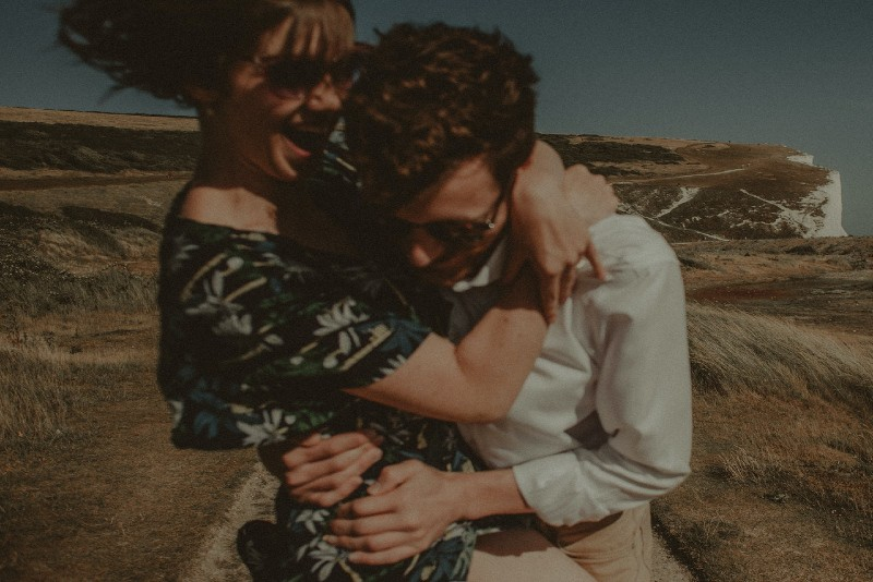 man in white shirt and woman with sunglasses hugging outdoor