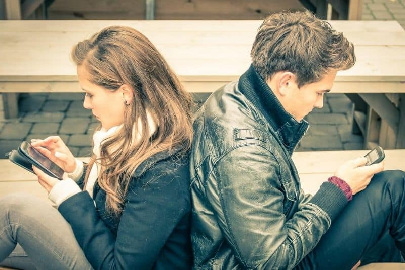 couple in the modern times looking at their cellphone back to back