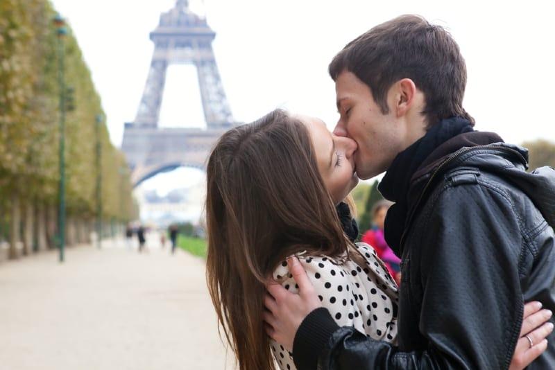 man and woman kissing near eiffel tower