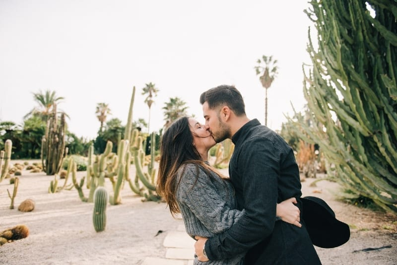 man and woman kissing while standing near cactus