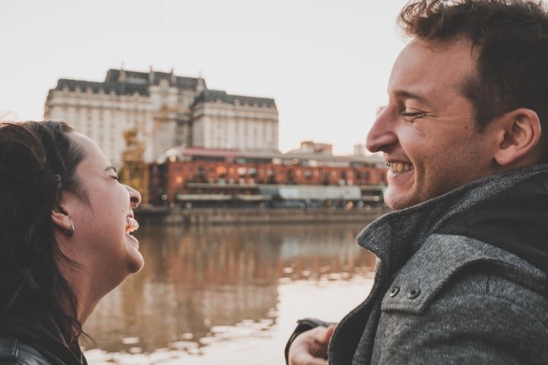 man and woman laughing while standing near water