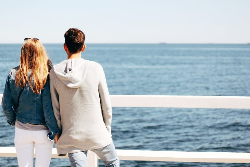 woman in denim jacket and man looking at sea