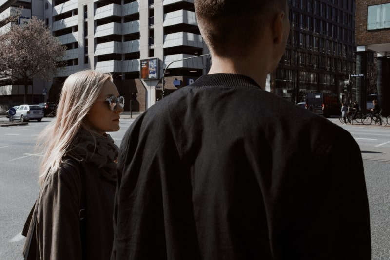 blonde woman with sunglasses and man looking at street
