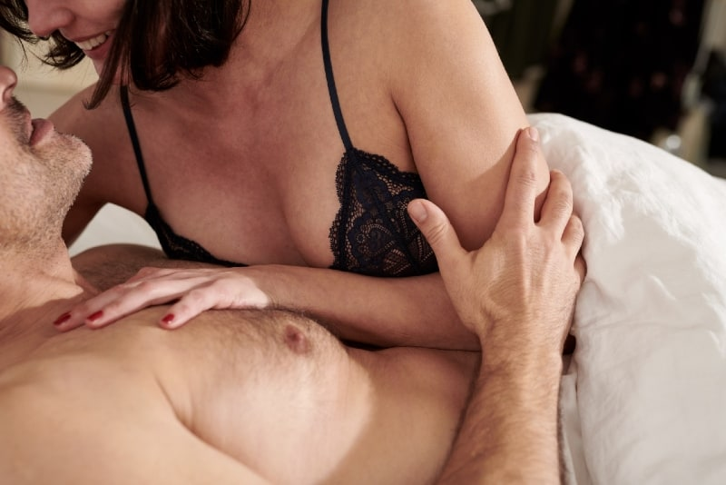 woman in black lace brassiere and man lying in bed