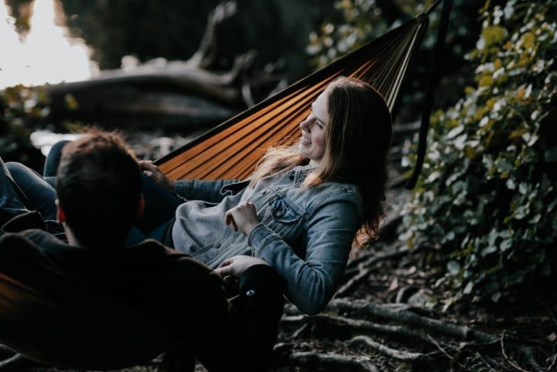 smiling woman in denim jacket and man lying on hammock