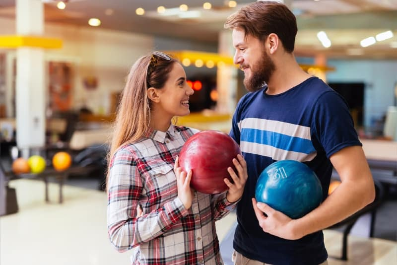 man and woman making eye contact while holding bowling balls