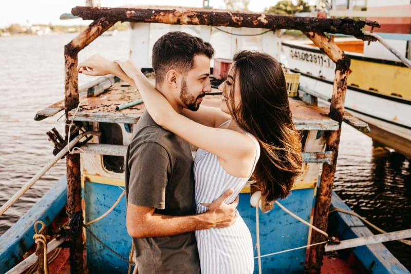 smiling man and woman making eye contact while hugging outdoor