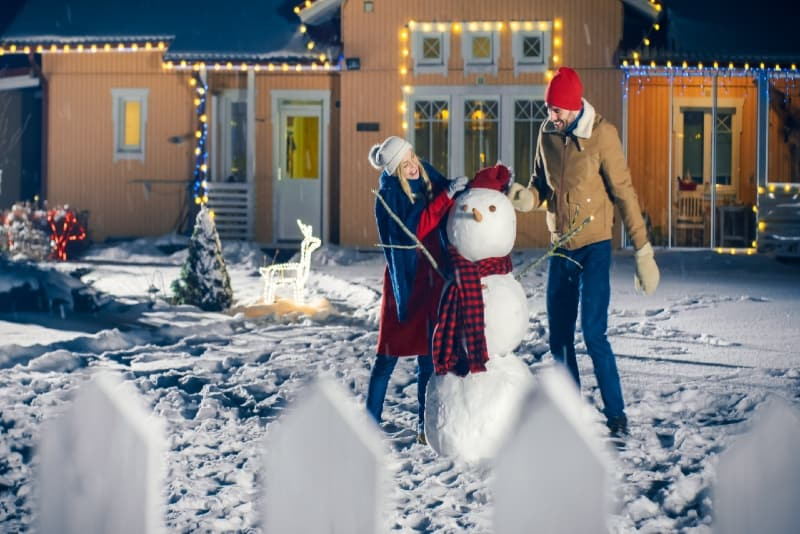man and woman making snowman backyard