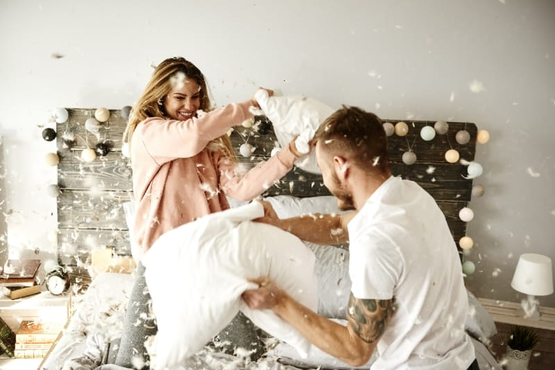 man and woman pillow fighting on bed