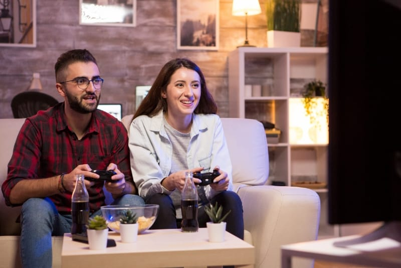 smiling man and woman playing video games at home