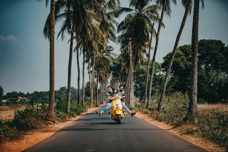 man and woman riding on motorcycle near palm trees