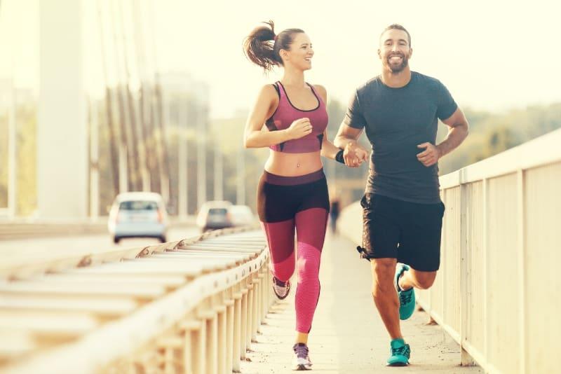 man and woman running on bridge