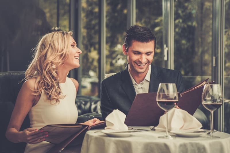 man and woman sitting at table and drinking wine