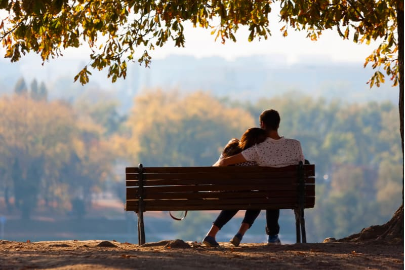 couple sitting silence on a wooden bench under a tree