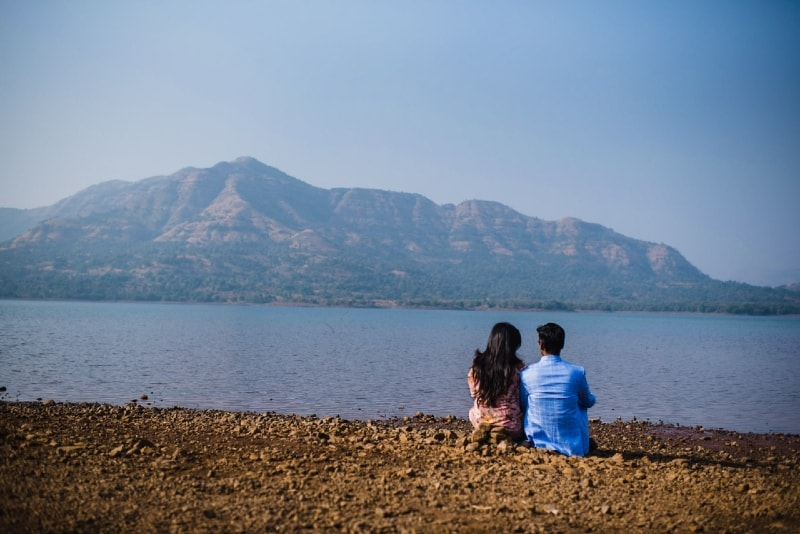 man with blue shirt and woman sitting near water