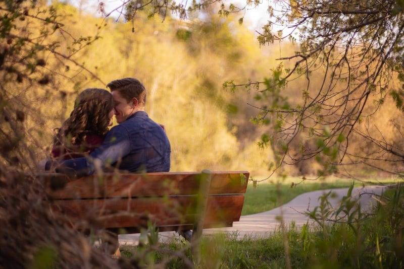 man hugging woman while sitting on bench