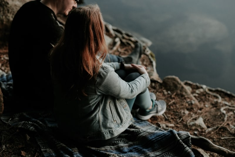 man and woman sitting on blanket near water