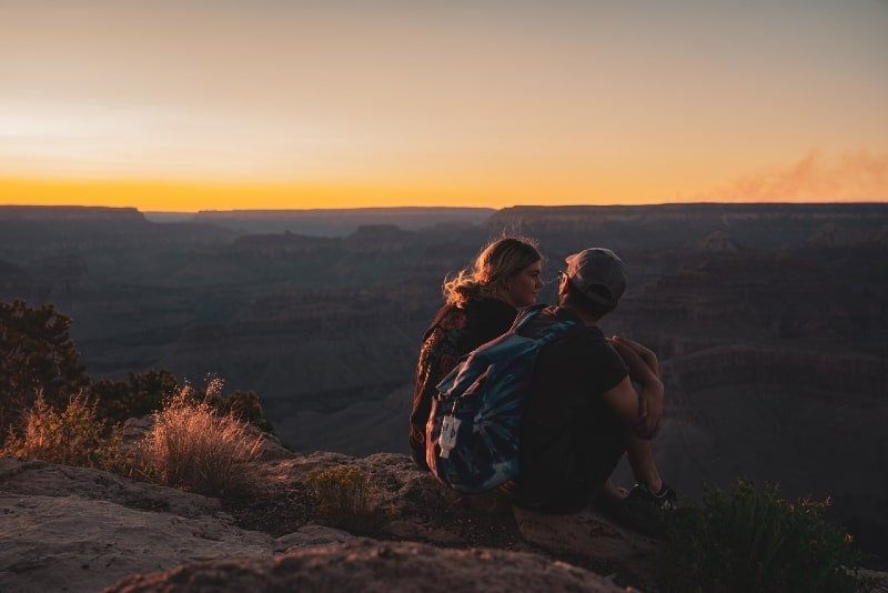 man with backpack and woman sitting on rock during sunset