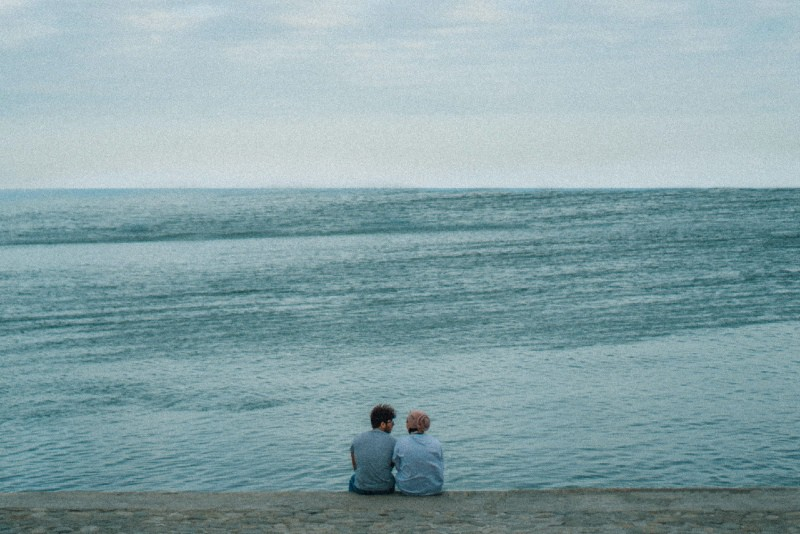 man and woman sitting on seashore looking at sea