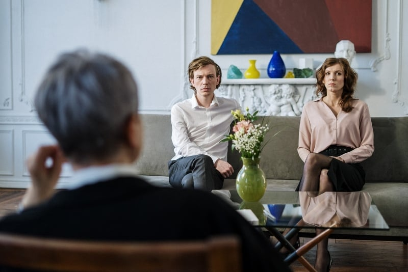 man in white shirt and woman sitting on sofa near therapist