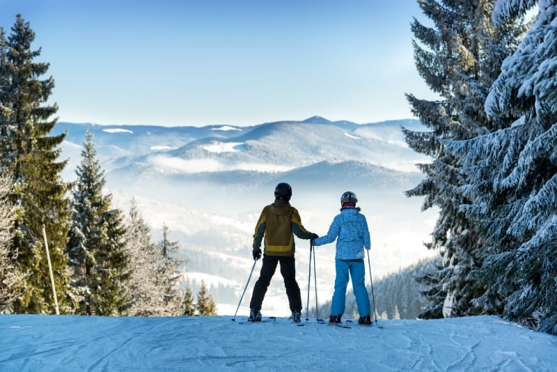 man and woman holding hands while skiing