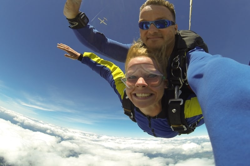 man with blue sunglasses and woman skydiving