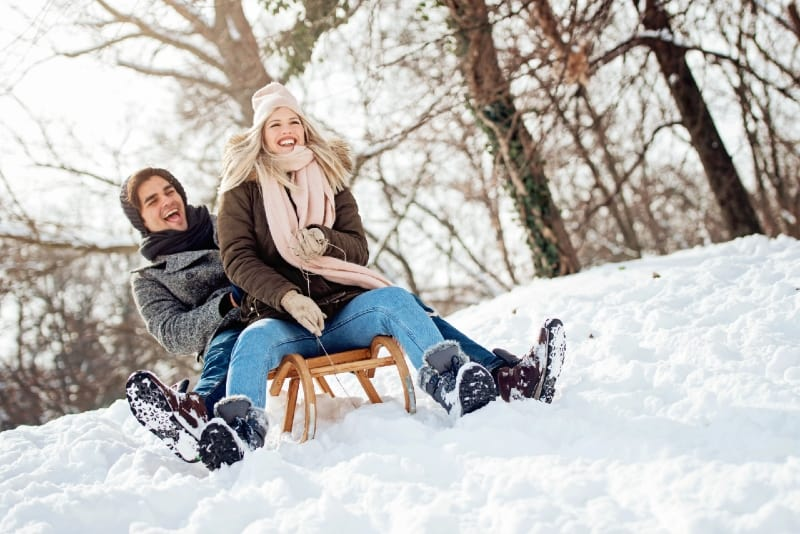 blonde woman with knit cap and man sliding on sled