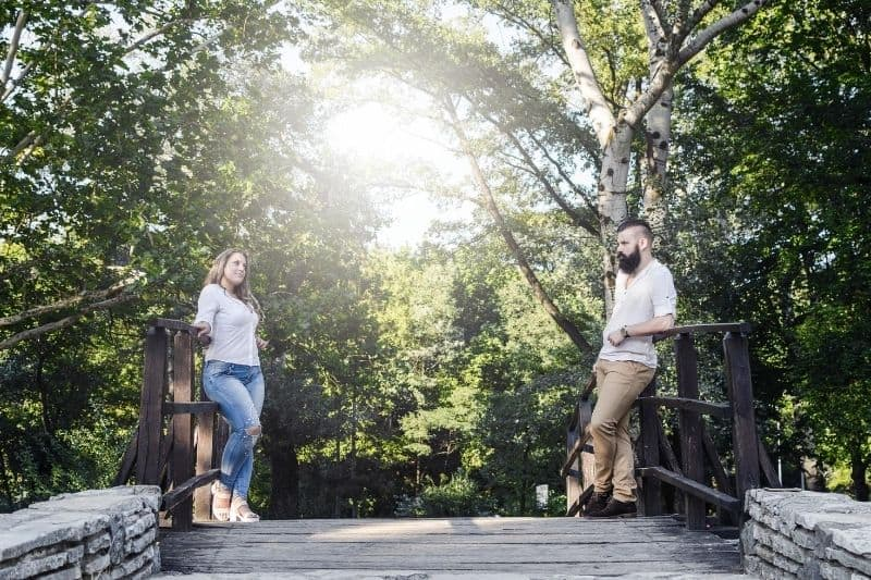 couple standing at wooden bridge looking at each other on thier first meeting