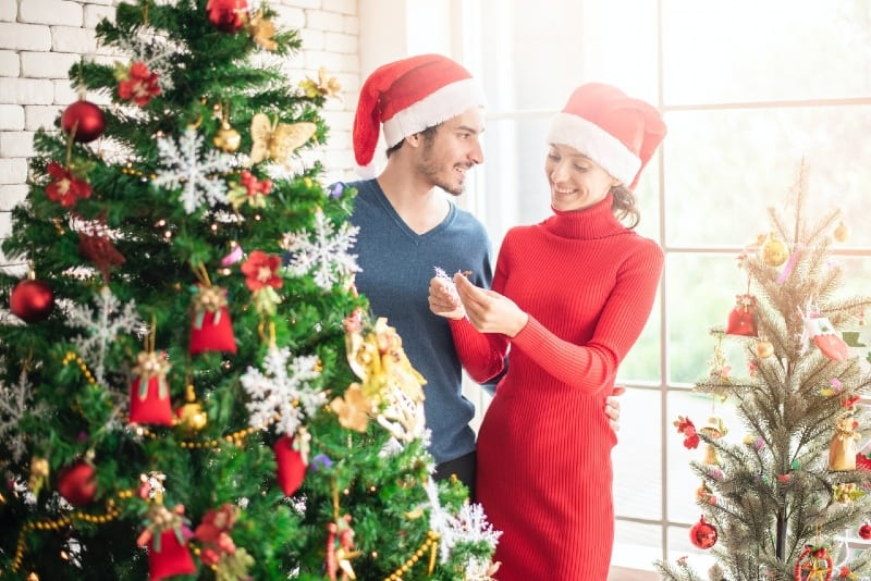 man and woman with red hats standing near christmas tree