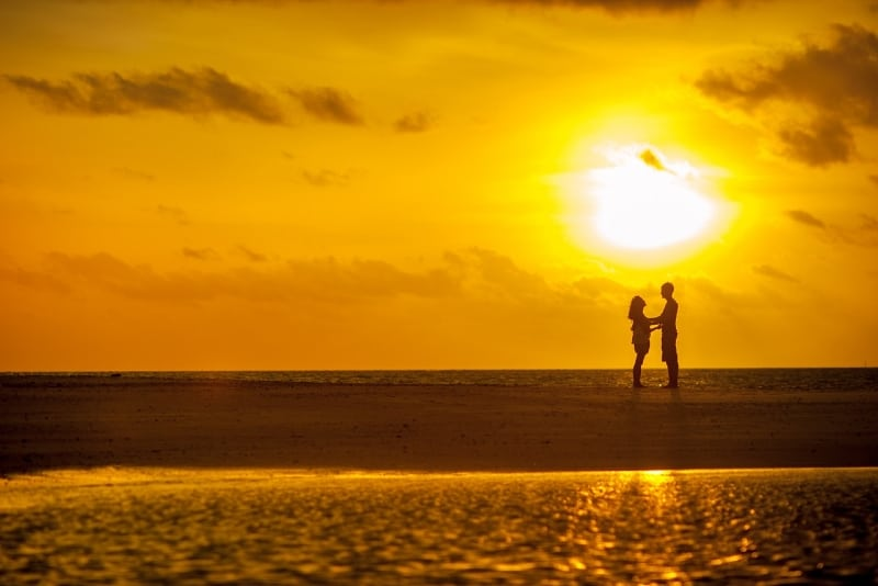 man and woman standing on seashore during sunset