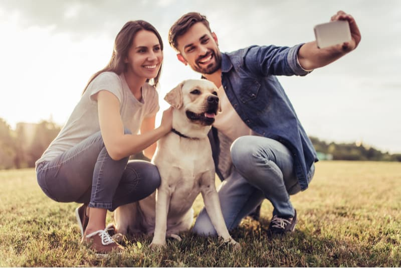 couple taking selfies with a dog squatting outdoors
