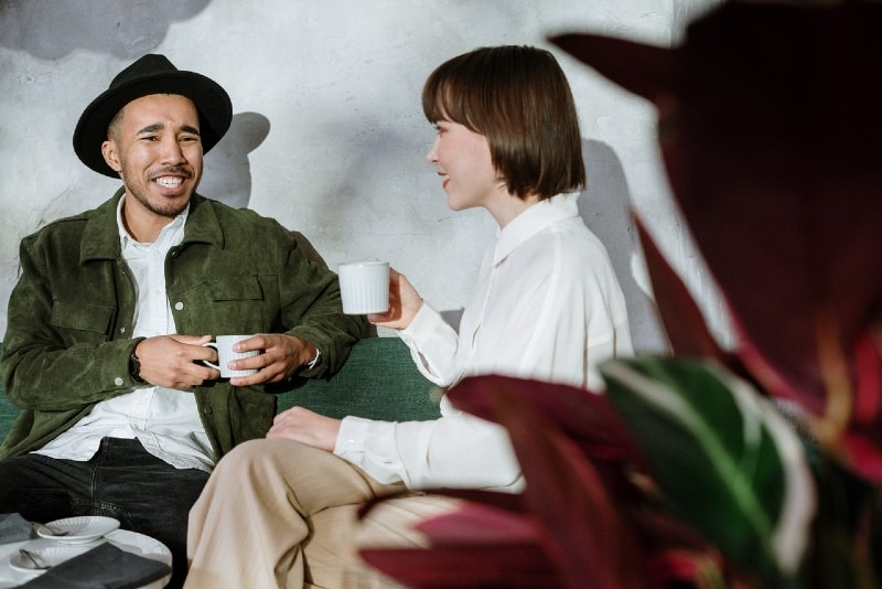 man with hat and woman talking while holding mugs