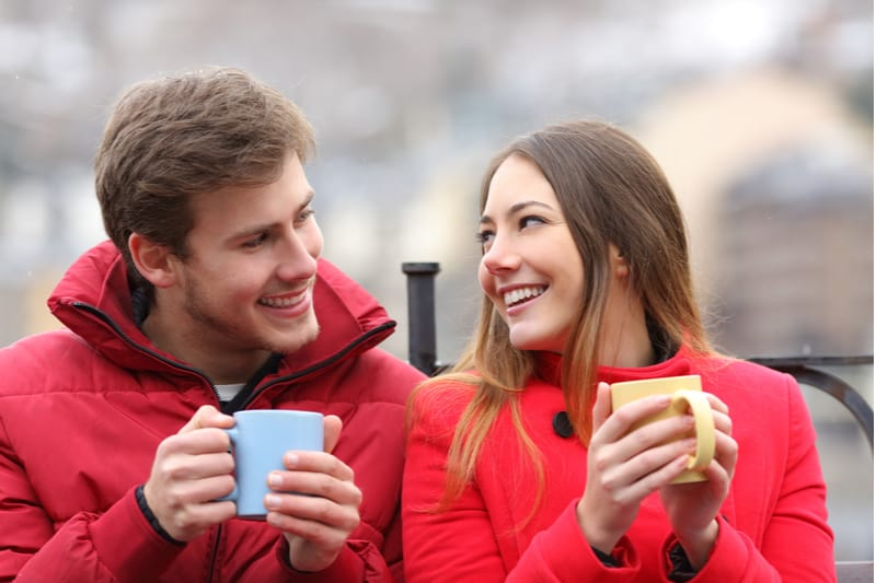 couple talking relaxed sitting on bench outdoors sipping coffee