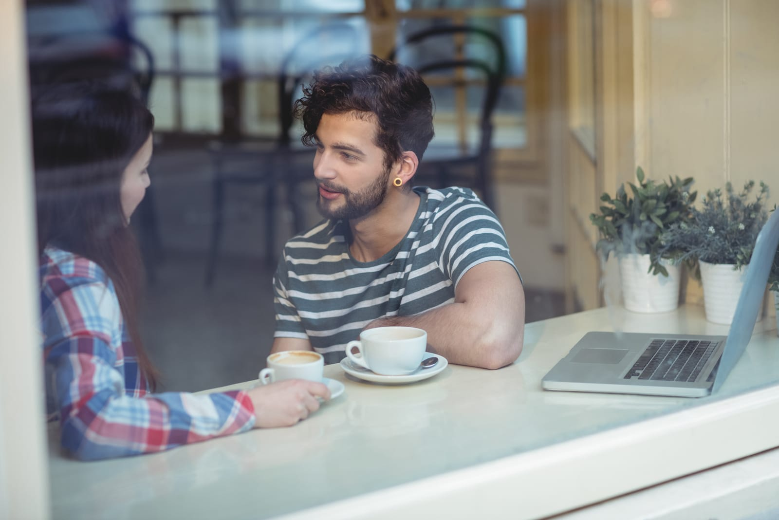 couple talking while sitting by window at cafe
