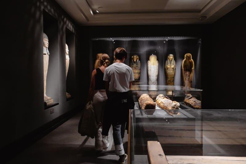man and woman walking near mummies in museum